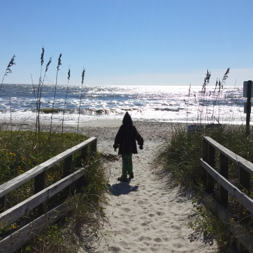 little boy walking onto the beach through a path in the dunes