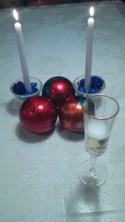 3 decorative balls with two lit candles and a glass of champagne